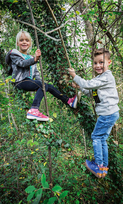 Children wearing Sympatex shoes play in the forest