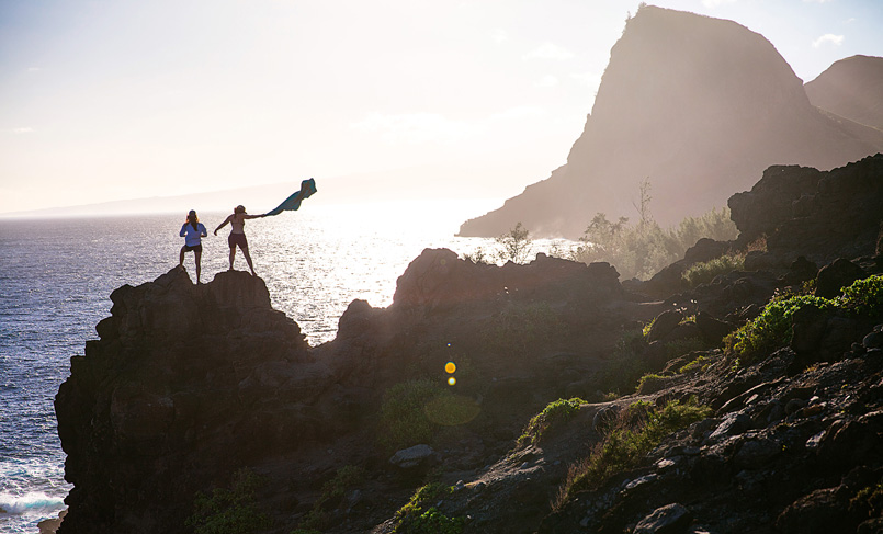 Two runners wearing Keen shoes standing on a rock in the sunset