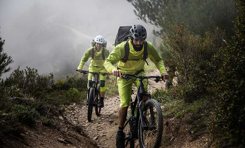 A man and a women biking in Vaude-clothes